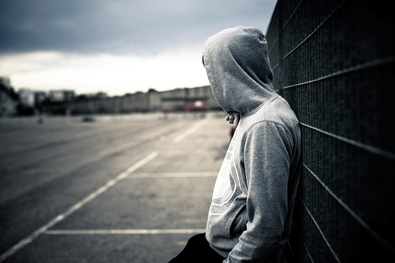 Hooded teen against a wall