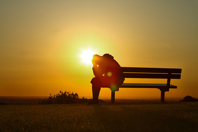Person sitting on bench at sunset